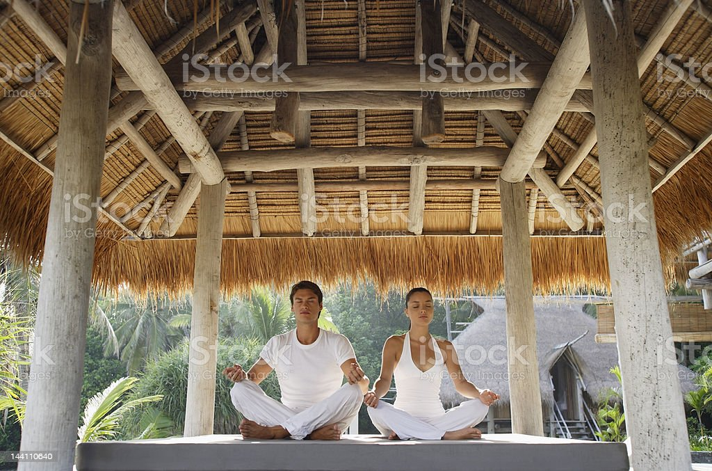 young couple doing yoga in outdoor sala stock photo