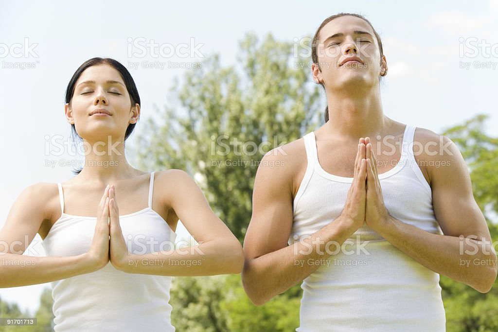 Young couple doing yoga moves or meditating together outdoors royalty-free stock photo