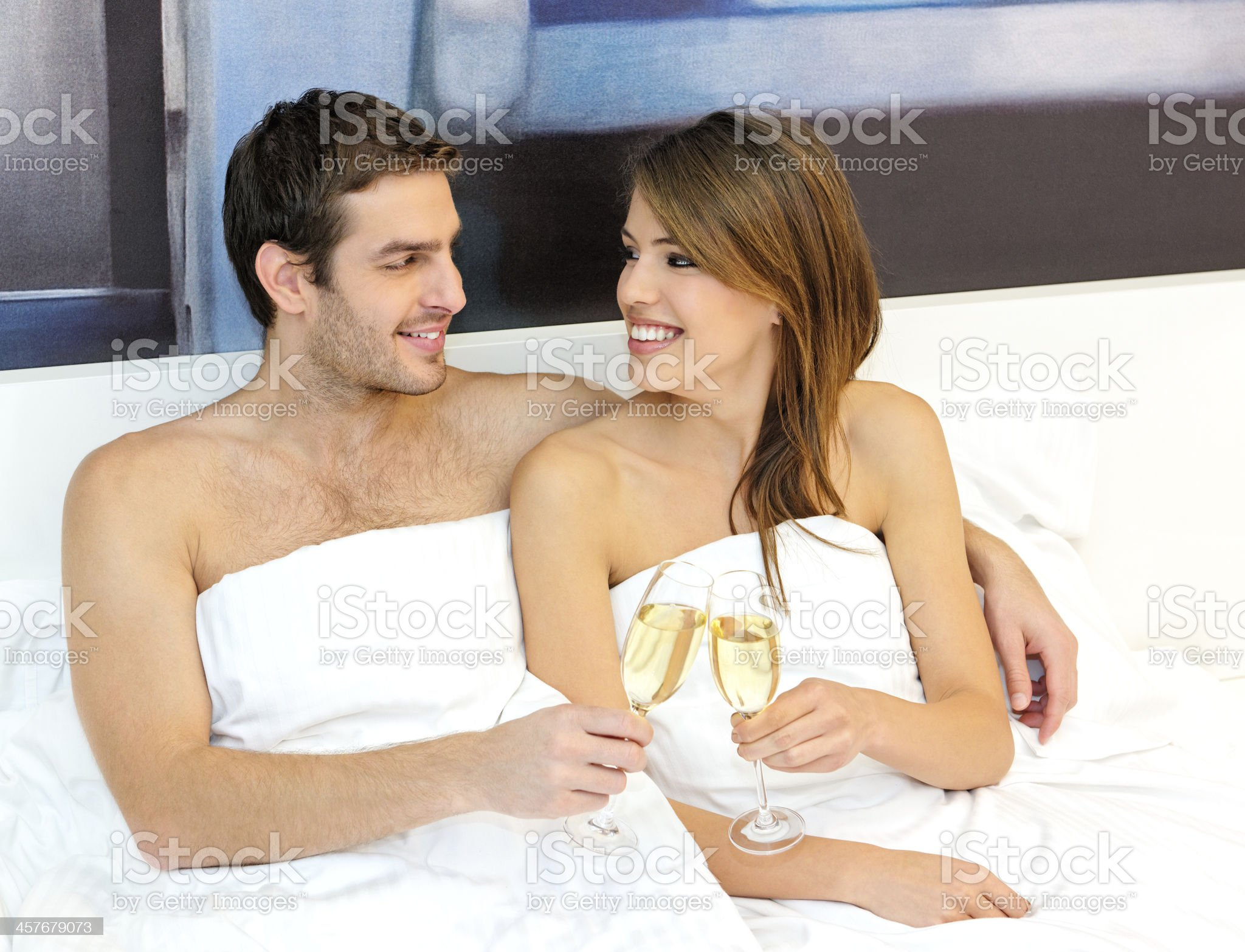Young Couple drinking champagne in bed royalty-free stock photo