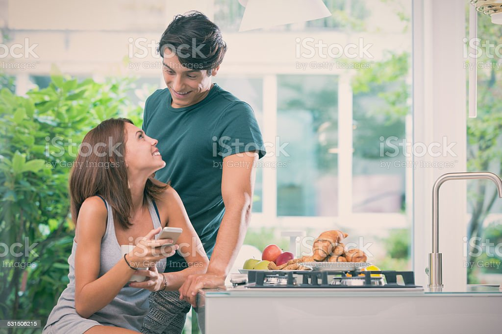 Young couple early in the morning chatter in the kitchen stock photo