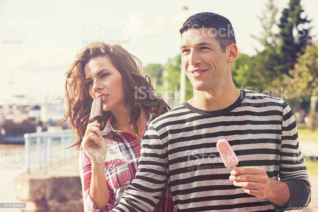 Young couple eating ice cream on a sunny day stock photo
