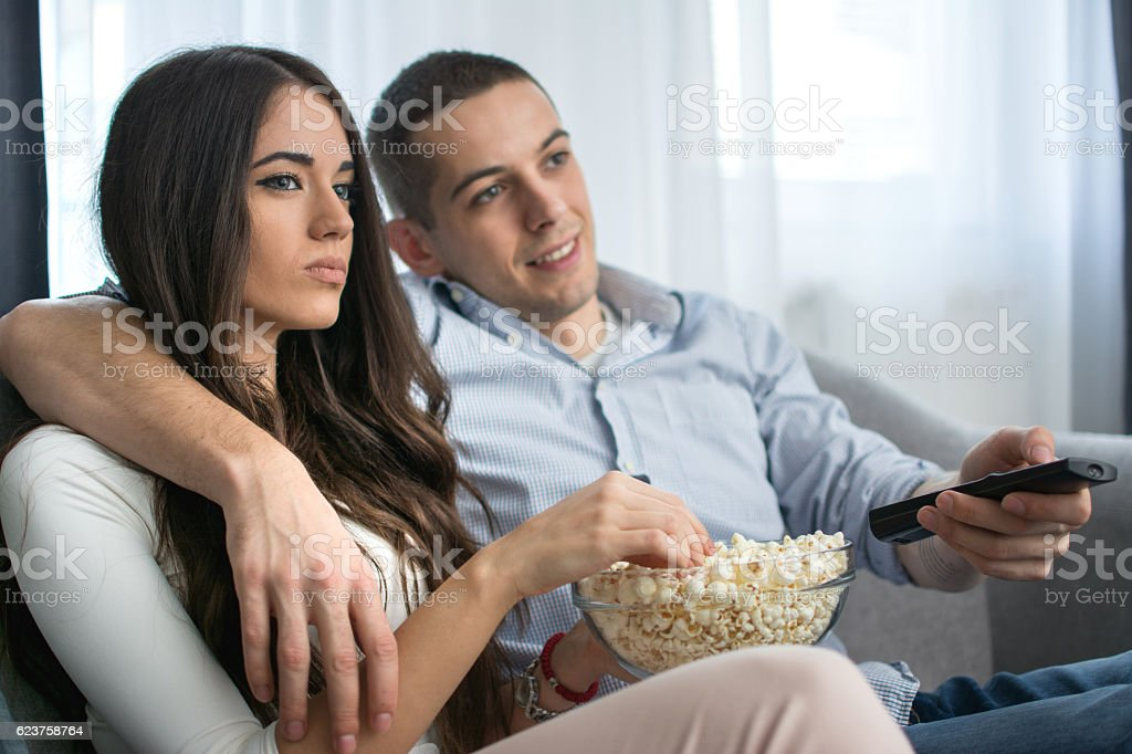 Young couple eating popcorn while watching tv at home.