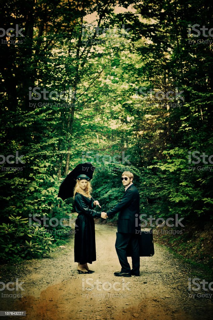 young couple elegantly dressed on a dirty road royalty-free stock photo