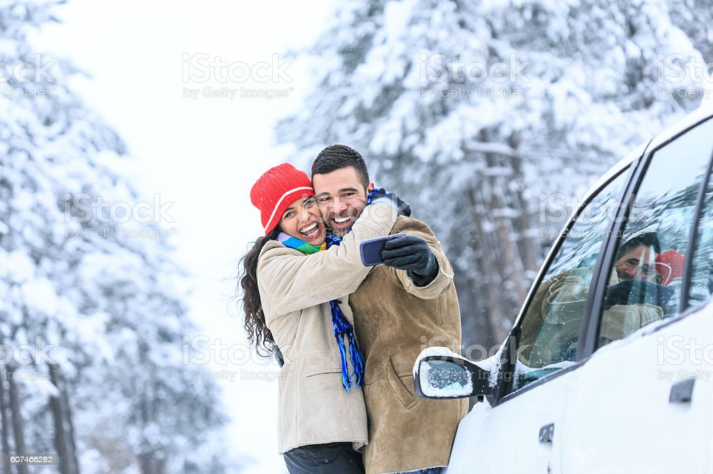 Young couple embracing and making selfie on snow footpath stock photo