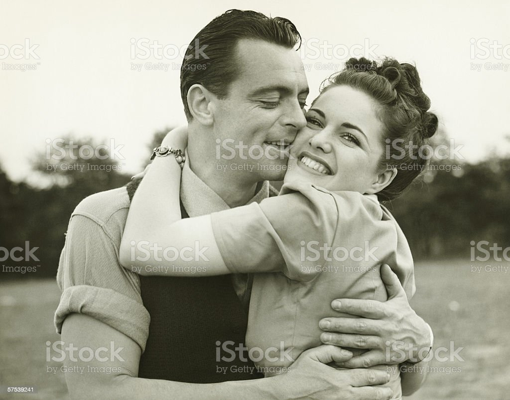 Young couple embracing in field, man kissing woman, (B&W) stock photo