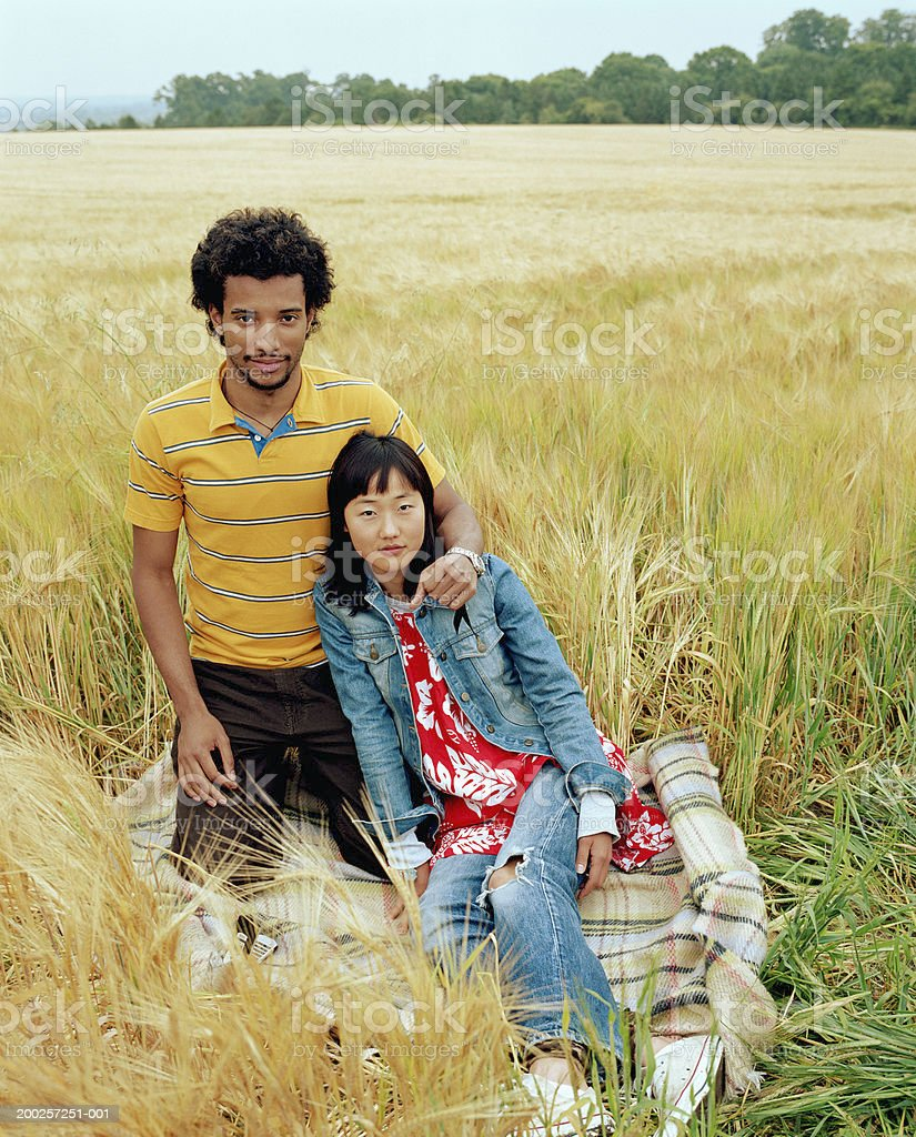 Young couple embracing on rug in field, portrait stock photo