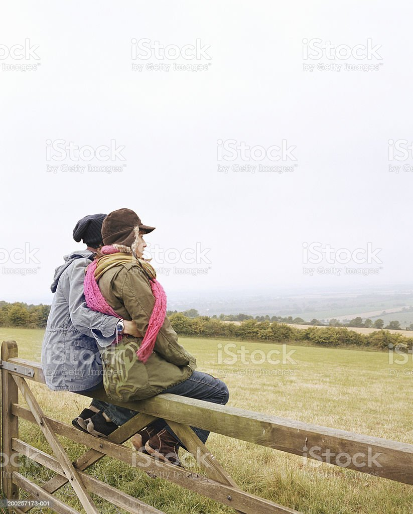 Young couple embracing, sitting on wooden fence by field royalty-free stock photo