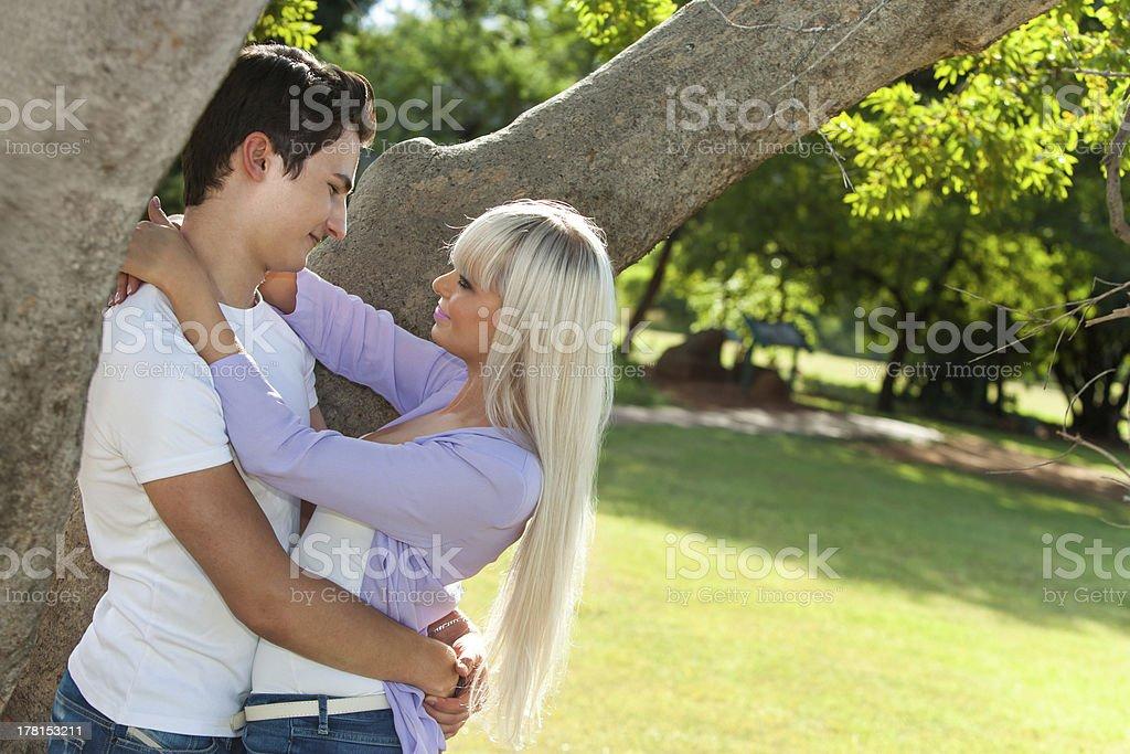 Jeune couple Embrasser sous arbre. photo libre de droits