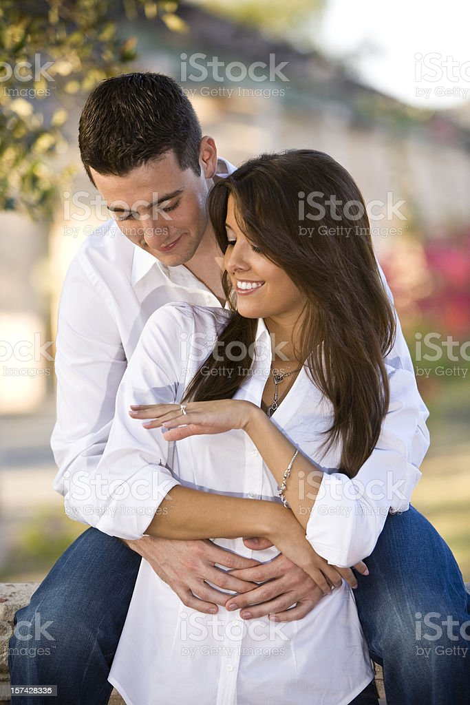 Young couple embracing while female shows off ring royalty-free stock photo