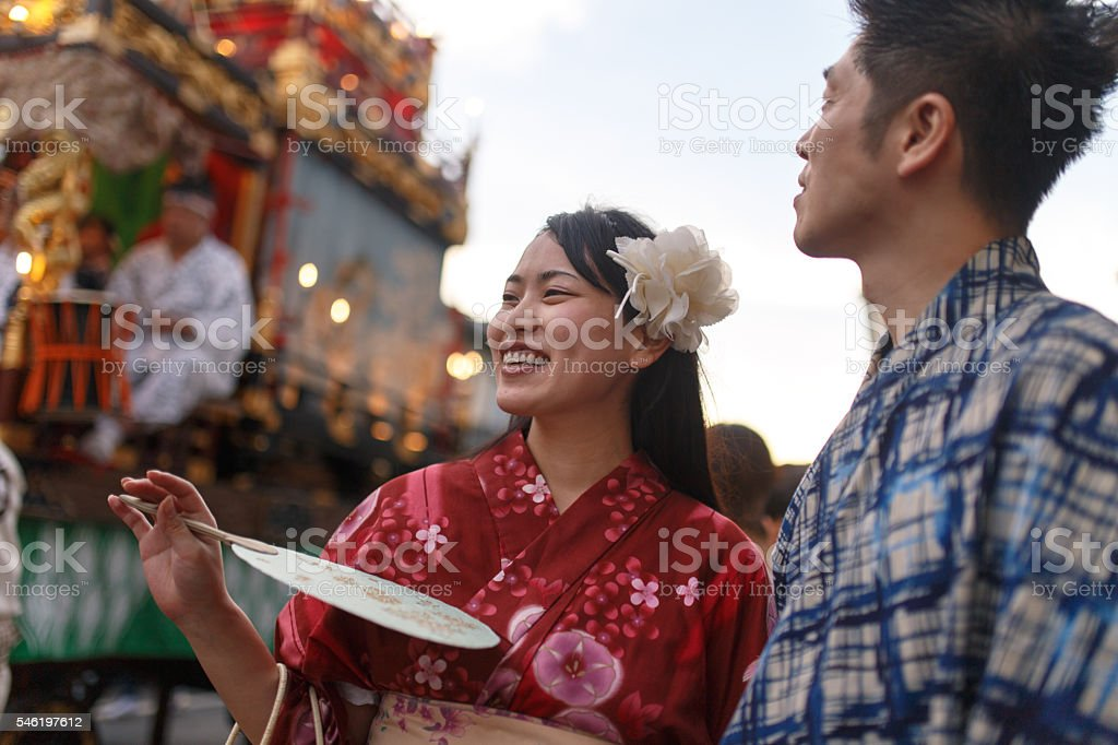 Young couple enjoy watching parade float at festival stock photo