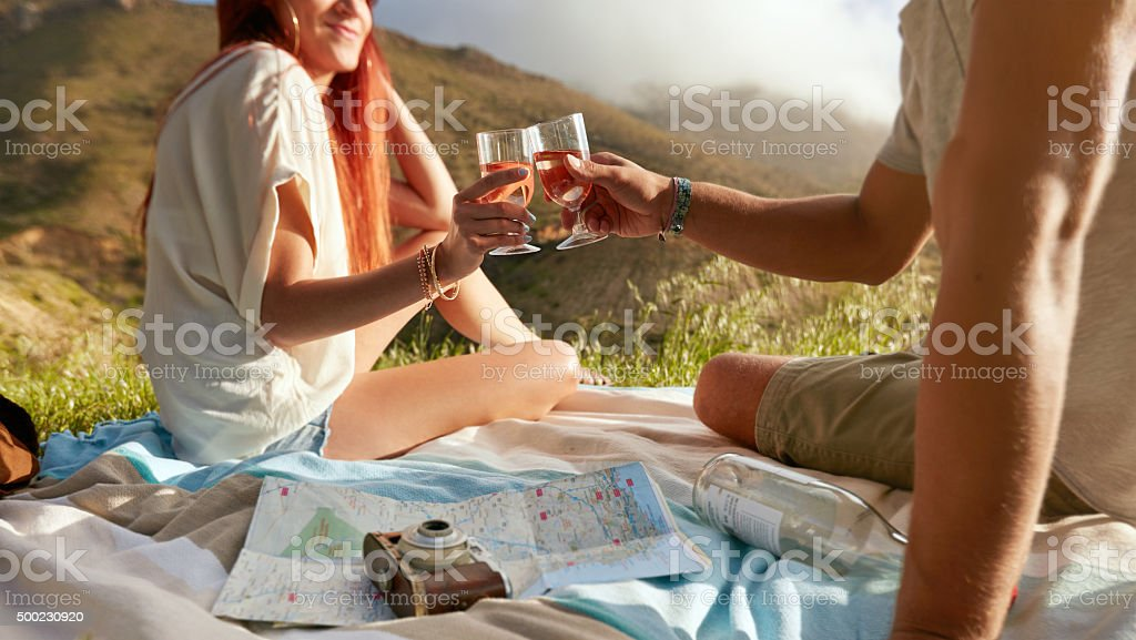 Young couple enjoying a picnic with wine. stock photo