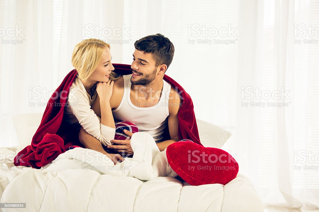 Young couple enjoying a  underneath the duvet stock photo
