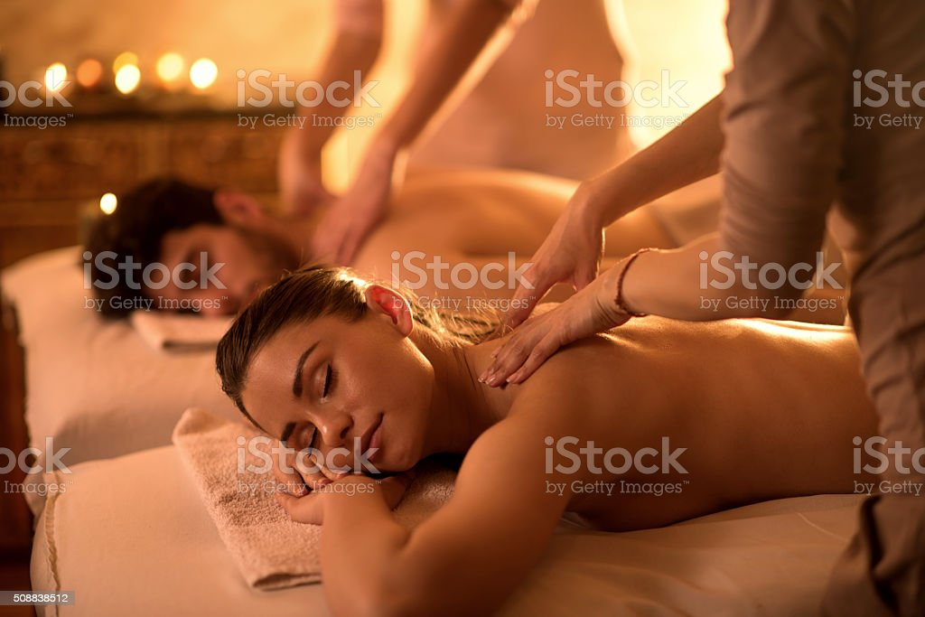 Young couple enjoying at spa during back massage. stock photo
