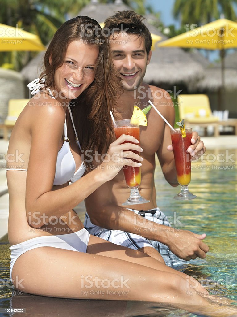 Young couple enjoying cocktail by the poolside royalty-free stock photo