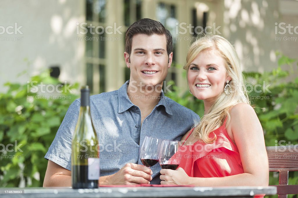 Young Couple Enjoying Glass of Wine in Outdoor Restaurant Hz royalty-free stock photo