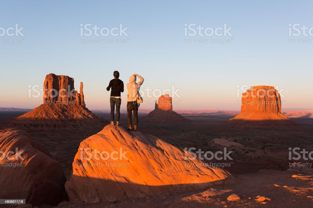 Young couple enjoying Monument Valley sunset stock photo