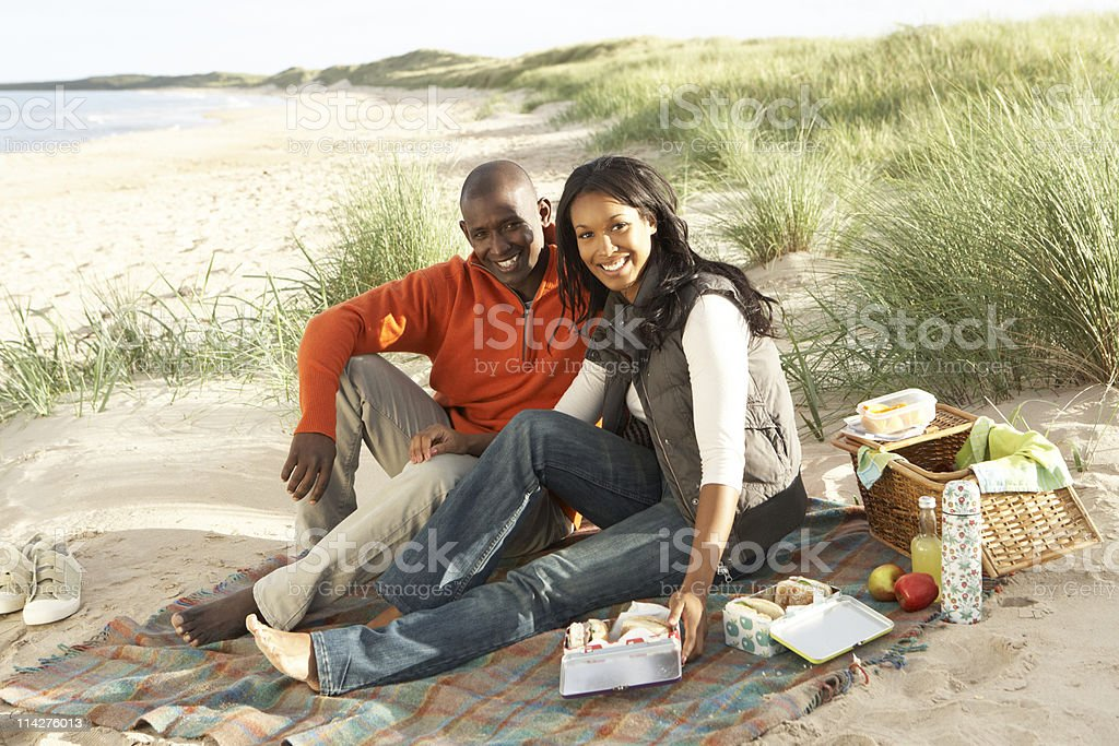 Young Couple Enjoying Picnic On Beach Together royalty-free stock photo