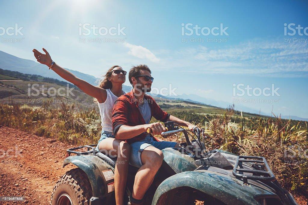 Young couple enjoying quad bike ride stock photo
