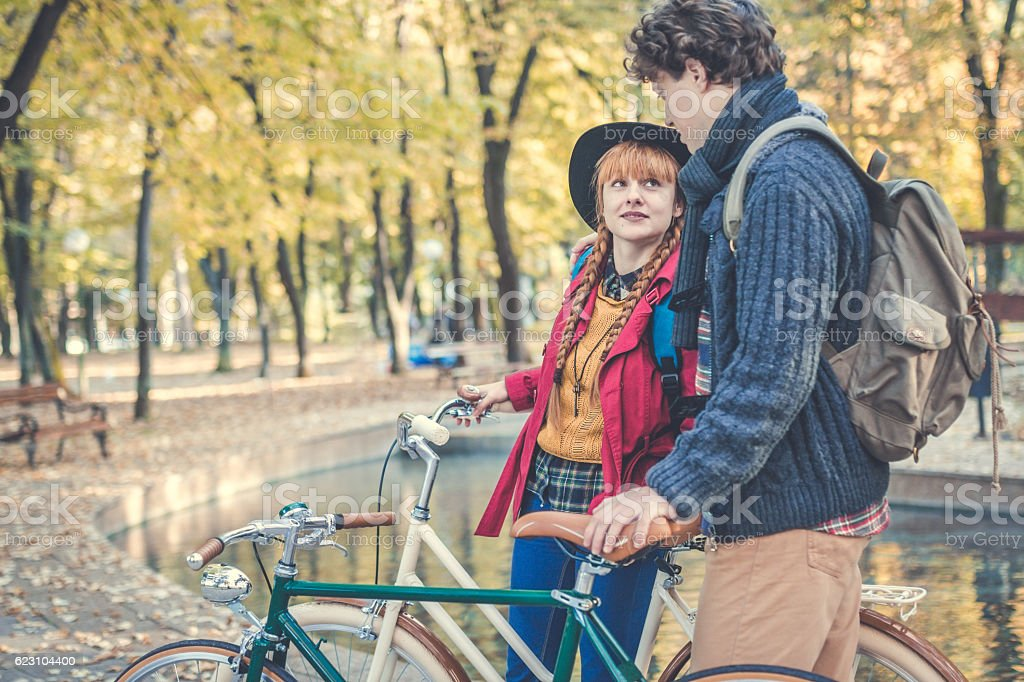 Young couple enjoying romantic ride with bicycle in autumn park stock photo