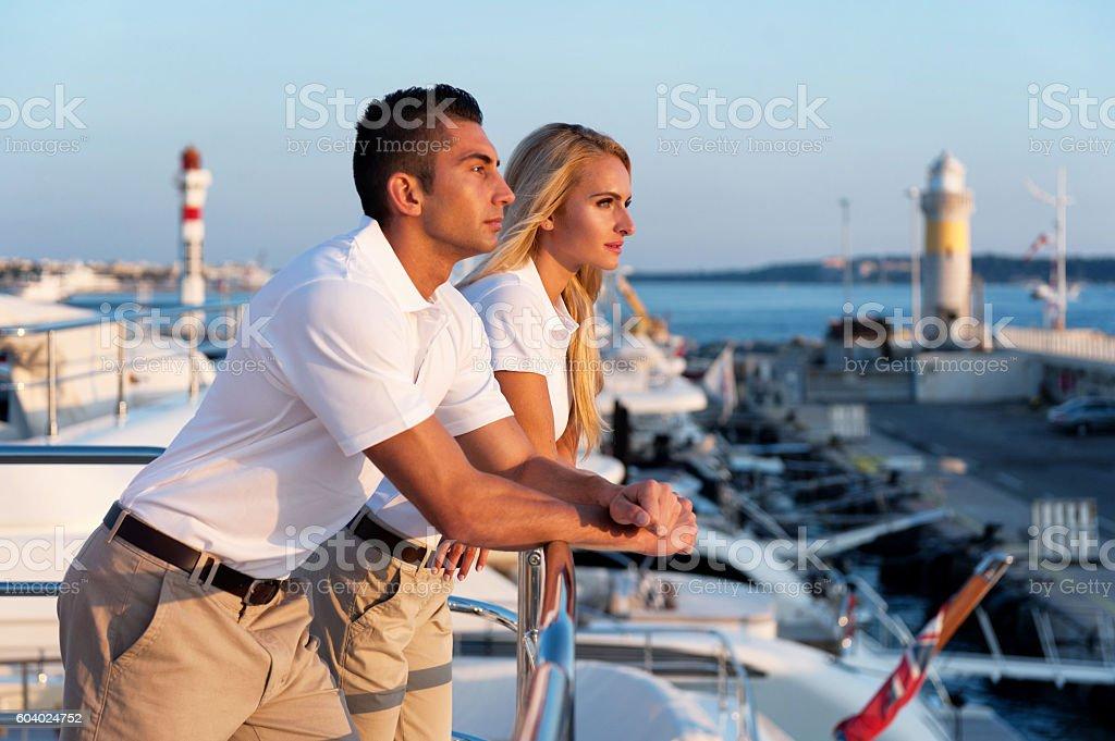 Young couple enjoying sunset on yacht stock photo