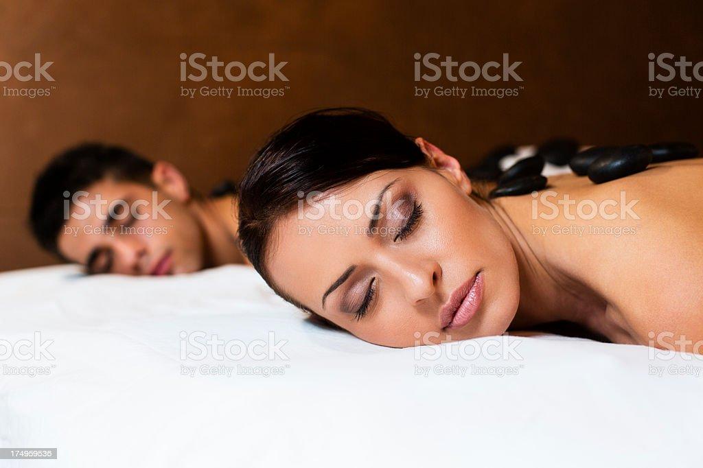 Young couple enjoying warm stone massage stock photo