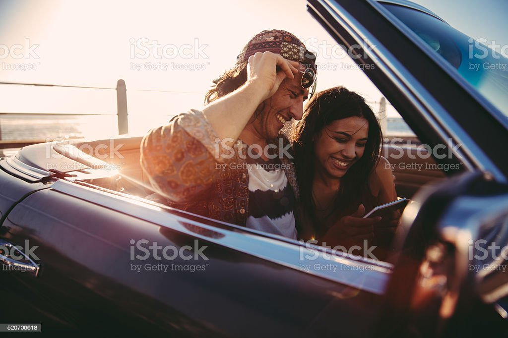 Young couple enjoys looking photos on smartphone on a convertible stock photo