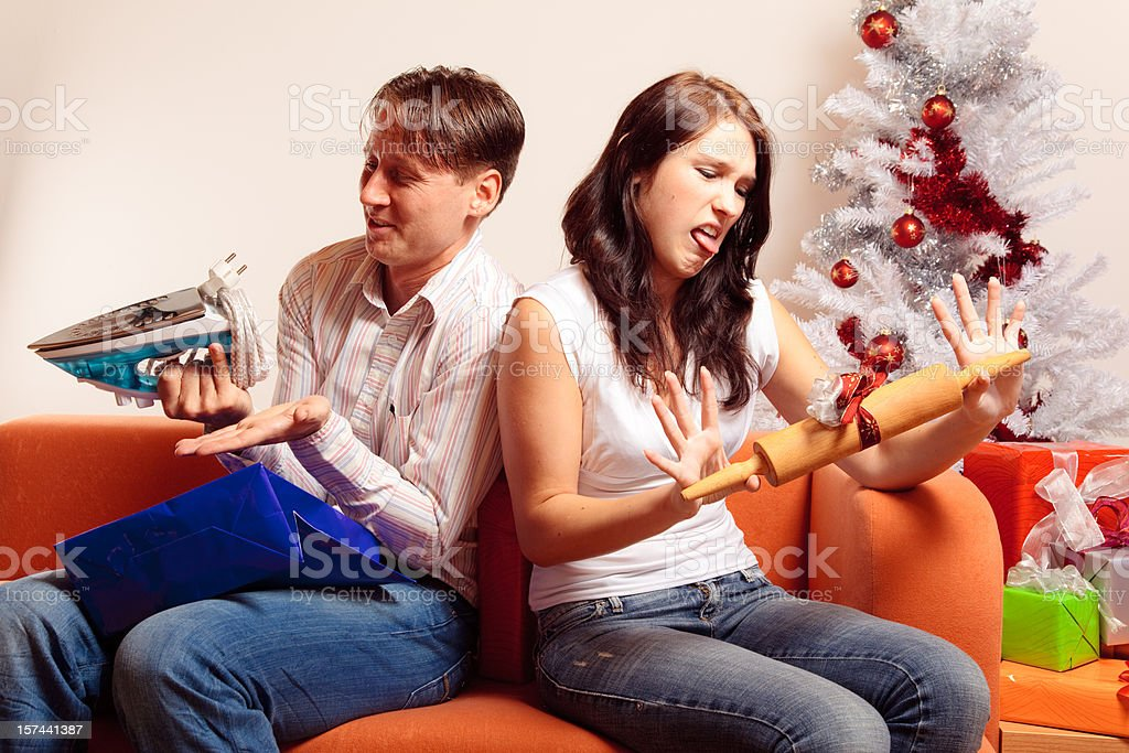 young couple exchanging christmas gifts (series) stock photo