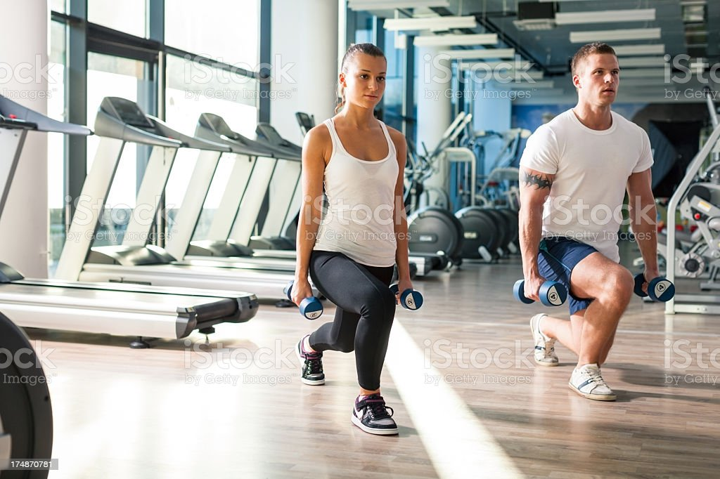 Young couple exercising at the fitness gym royalty-free stock photo