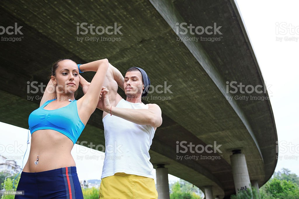 Young couple exercising in the park stock photo