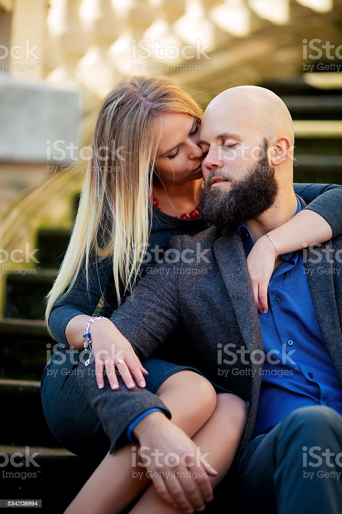 Young couple eyes closed, stylishly dressed, sitting on the steps, royalty-free stock photo
