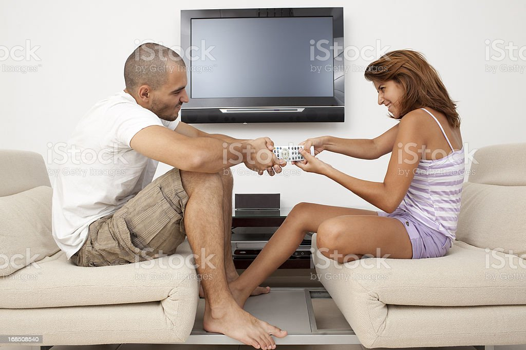 A Young couple arguing over TV remote control.