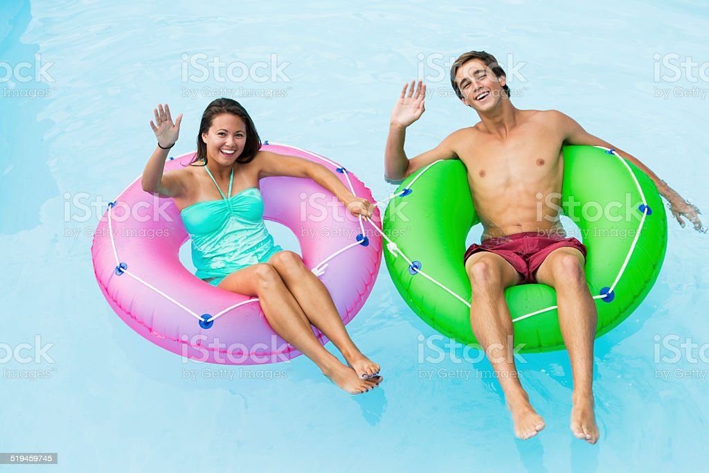 Young couple floating on innertubes stock photo