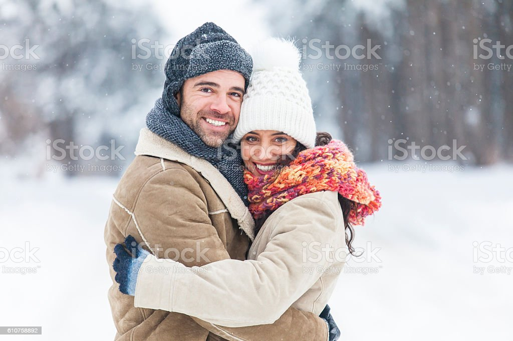 Young couple freezing and embracing in snow forest stock photo