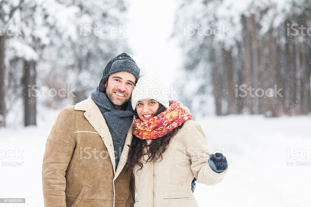 Young couple freezing and standing close in snow forest stock photo