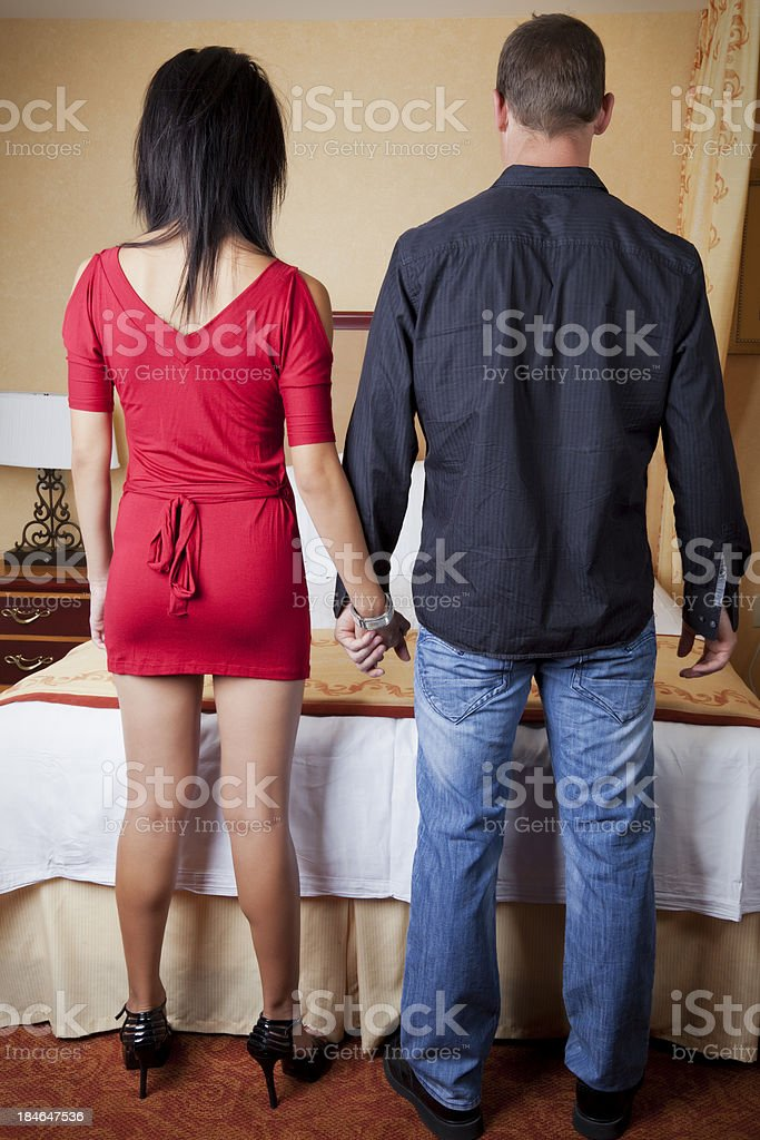 Young couple from the back in hotel room stock photo