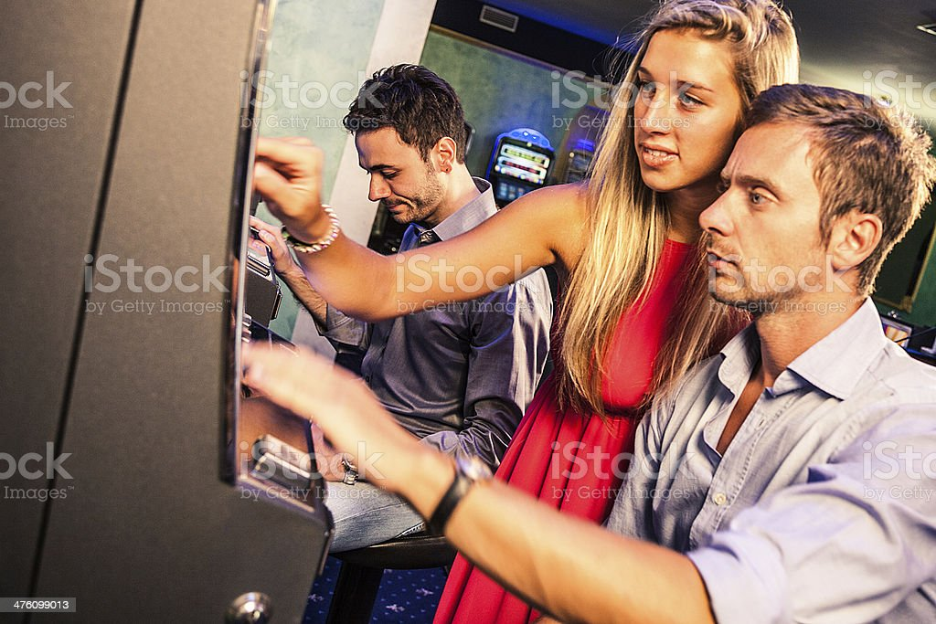Young couple gambling on slot machines royalty-free stock photo