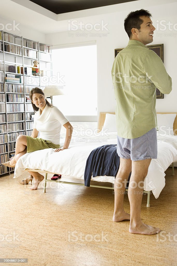 Young couple getting dressed for work in bedroom stock photo