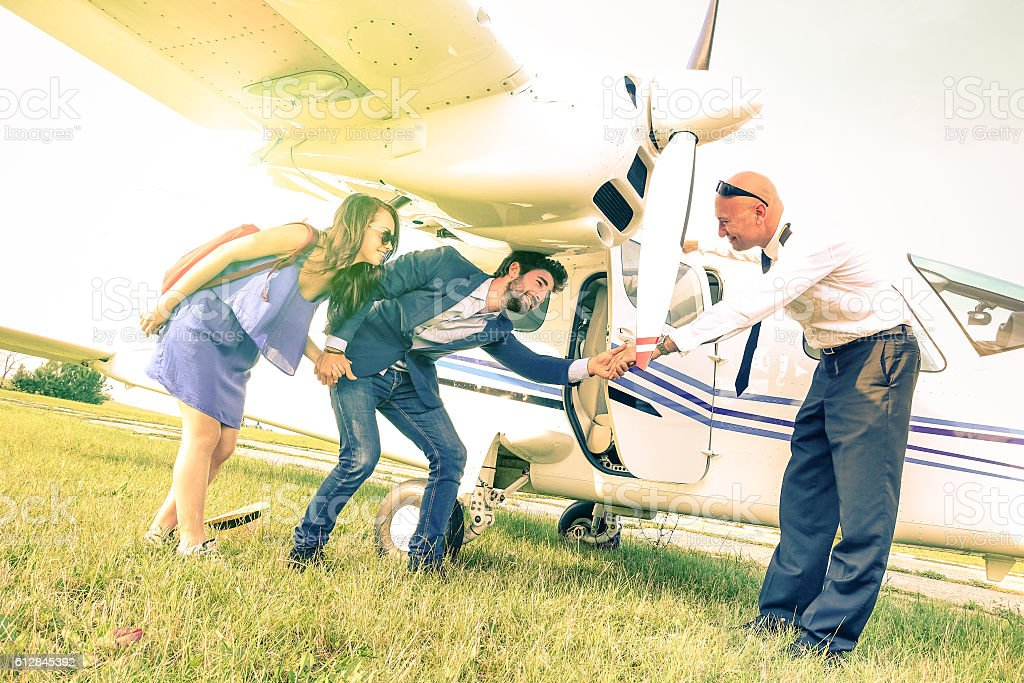 Young couple getting on lightweight airplane with captain welcome stock photo