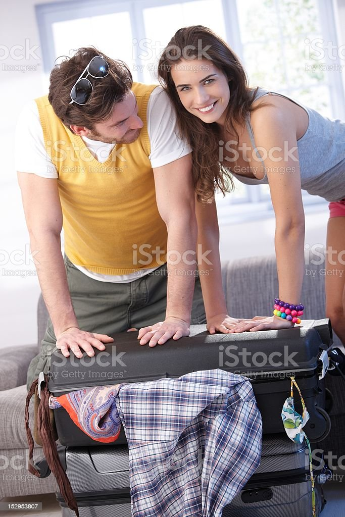 Young couple going to summer vacation packing bag royalty-free stock photo