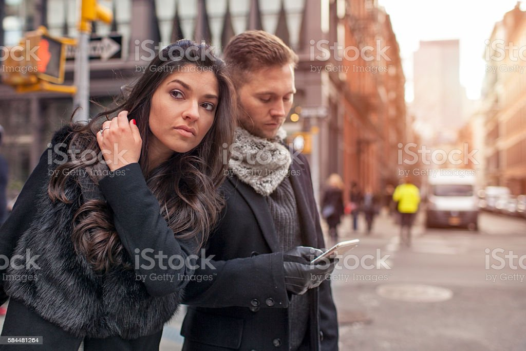 Young couple hailing taxi via mobile phone stock photo