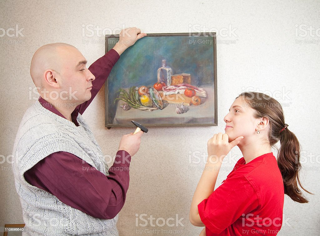 Young couple hanging art picture on wall at royalty-free stock photo