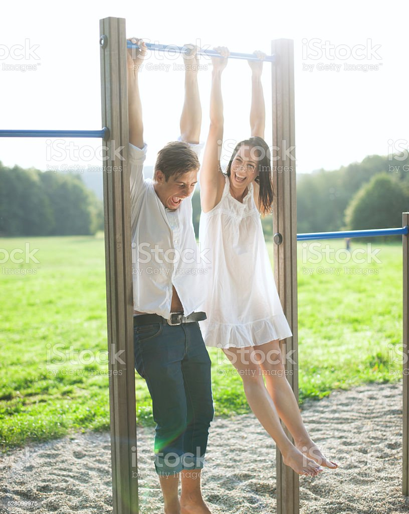 Young couple hanging on bars at playground stock photo