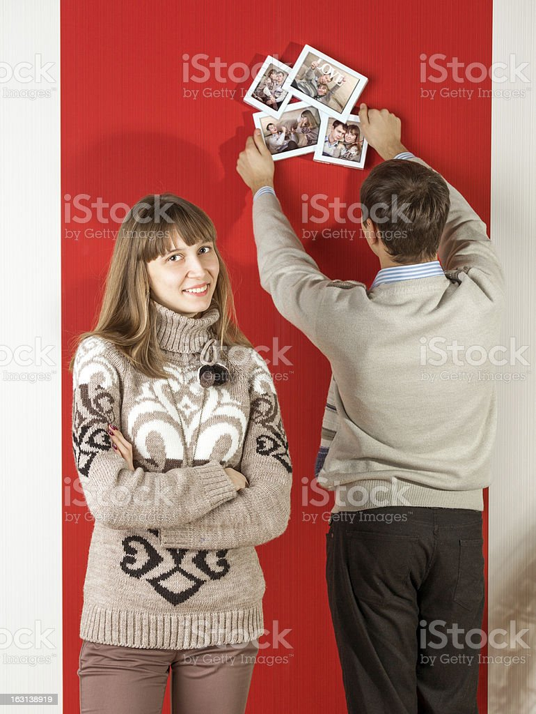 Young couple hanging up picture frame, woman smiling royalty-free stock photo