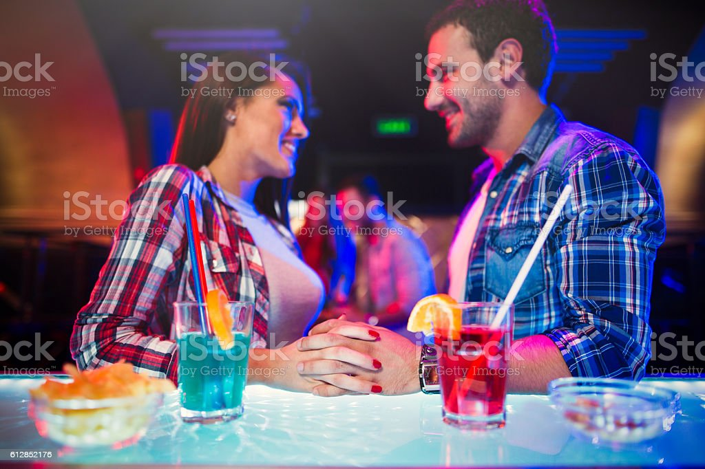 Young couple happily flirting over drinks at  night club stock photo
