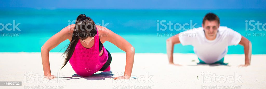 Young couple happy working out in sand on beach stock photo