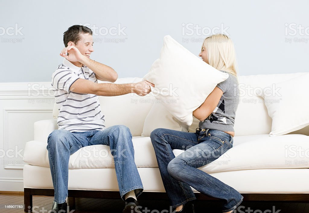Young Couple Having a Pillow Fight on Sofa royalty-free stock photo