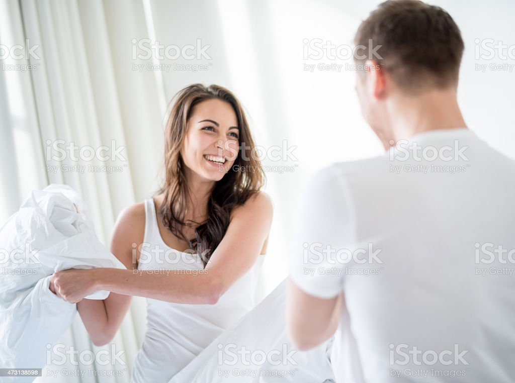 Young couple having a pillow fight in the bedroom and looking playful