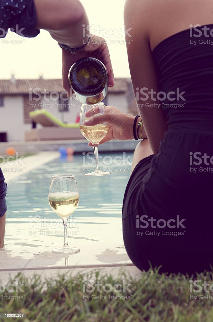 Young couple having aperitif near the swimming pool royalty-free stock photo