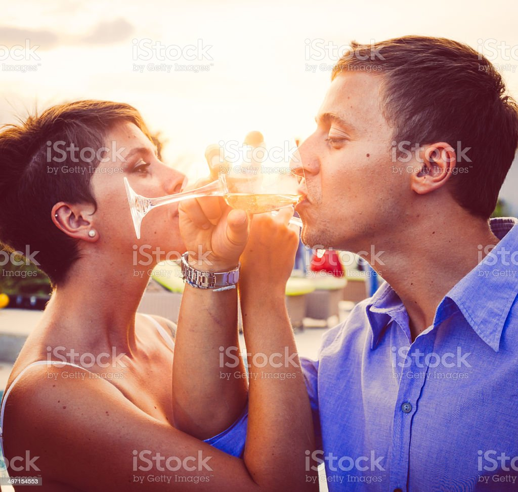 Young couple having aperitif near the swimming pool stock photo