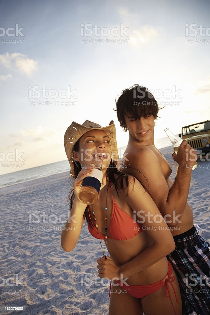 Young couple having beer with jeep in background on beach royalty-free stock photo